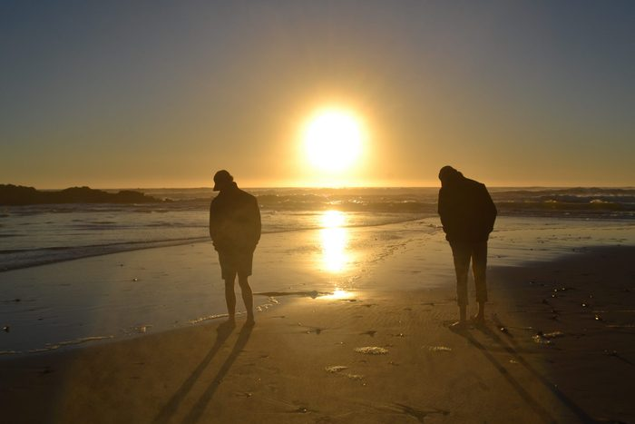 Two brothers silhouetted at sunset