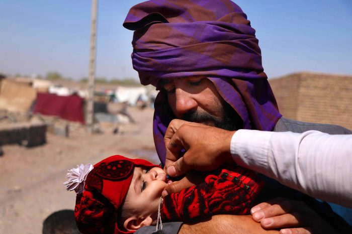 A health worker administers a Polio vaccination to a child at a camp setup by the World Vision NGO and UNICEF in Herat, Afghanistan, 08 August 2018.