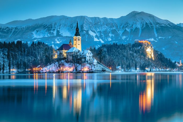 Beautiful twilight view of Lake Bled with famous Bled Island and historic Bled Castle in the background during scenic blue hour at dawn in winter, Slovenia