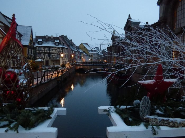 Christmas decorations : red balls, wooden red star, fir branches, fresh snow.Sunrise, streets lights, Colmar, Alsace, France.Can be used for editorial and commercial purposes.