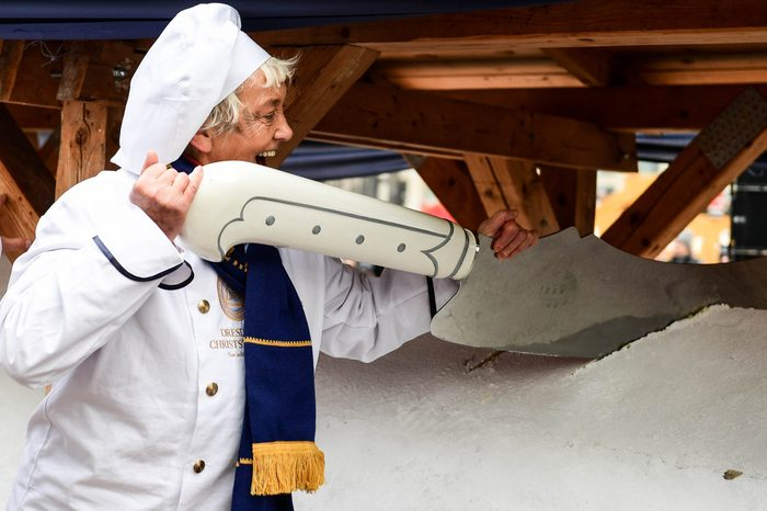 A Dresdener baker uses giant knife as she slices a giant Stollen cake during the 26th Dresden Stollen Festival in Dresden, Germany, 07 December 2019. The Stollen festival tradition dates back to 1730 and takes place on the Saturday before the second Sunday in Advent. Before the festival the members of the Stollen Association bake over 200 trays of stollen that are then assembled to one giant stollen. The huge cake, which weighs about 3960 kg, was paraded through the streets accompanied by a marching band. The giant cake is cut into thousands of pieces with the Stollen knife then sold to people at the festival. 7 Dec 2019
