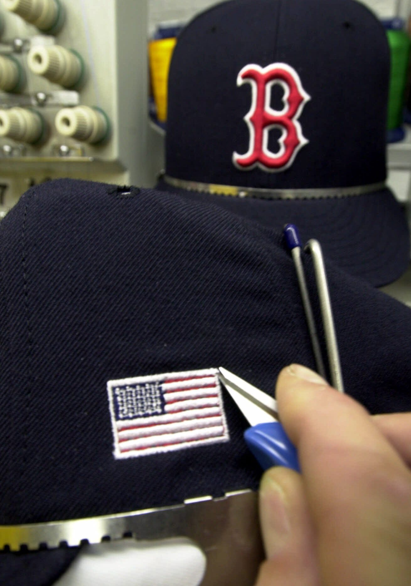 Mandatory Credit: Photo by David Duprey/AP/Shutterstock (6465200a) MAJOR LEAGUE CAPS A worker stiches an American flag into a baseball cap at the New Era Cap Company in Buffalo, N.Y., . The company is stitching American flags onto the caps of Major league baseball players to wear when play is resumed after Tuesday's terrorist attacks in New York and Washington. The cap maker's plants in Jackson, Ala., and Buffalo will handle the last-minute order from the league. Flags about an inch-high will appear on the caps' left side ATTACKS BASEBALL CAPS, BUFFALO, USA