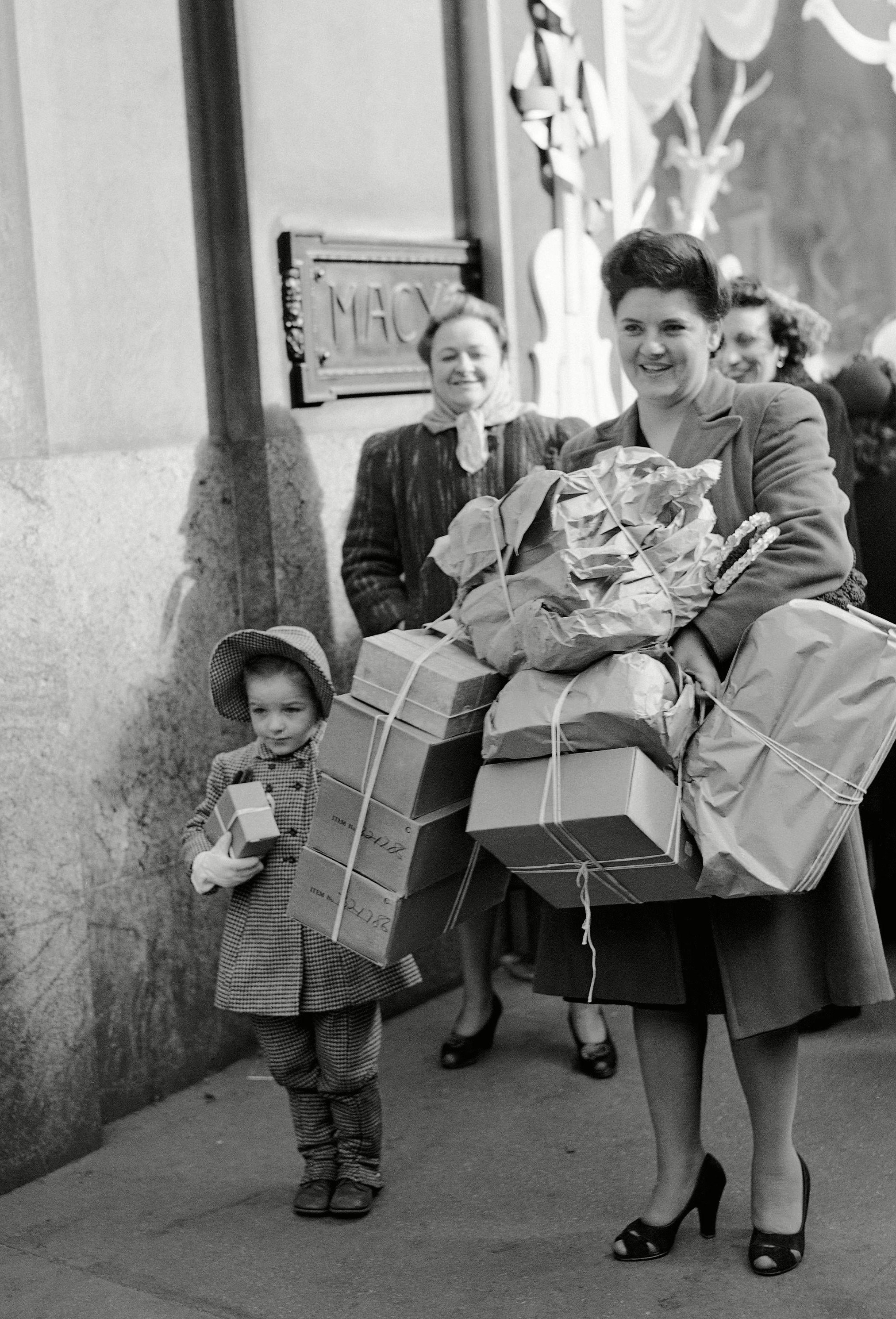 """Mrs.Frances Corless her daughter """"Chickie"""" are loaded down with bundles after doing some last minute shopping at Macy's on Christmas Eve in New York"""