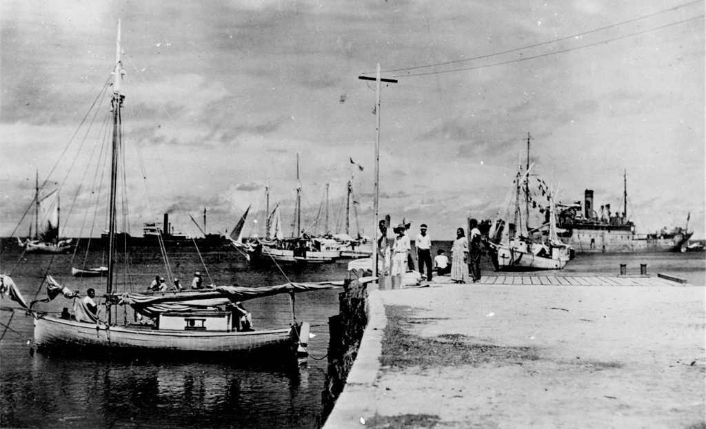 """This undated photo discovered in the U.S. National Archives by Les Kinney shows people on a dock in Jaluit Atoll, Marshall Islands. A new documentary film proposes that this image shows aviator Amelia Earhart, seated third from right, gazing at what may be her crippled aircraft loaded on a barge. The documentary """"Amelia Earhart: The Lost Evidence,"""" which airs, on the History channel, argues that Earhart and her navigator, Fred Noonan, crash-landed in the Japanese-held Marshall Islands, were picked up by Japanese military and that Earhart was taken prisoner"""