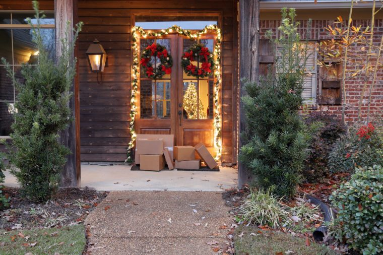 Boxes and packages next to front door during holiday christmas season, with Christmas lights and wreaths