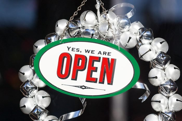 Festive Christmas decorations and open sign with jingle bell wreath hanging in shop store window door during holiday shopping season