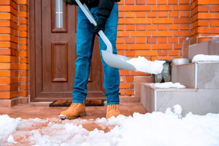 figure shoveling snow and ice off the front porch of their home
