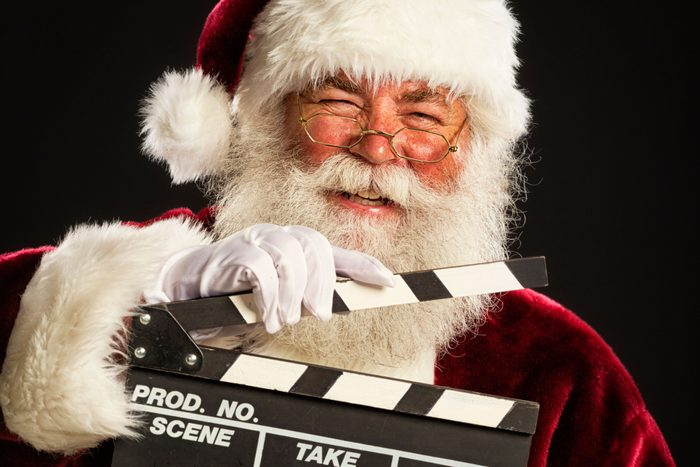 Smiling Santa holding a movie clap board on black background