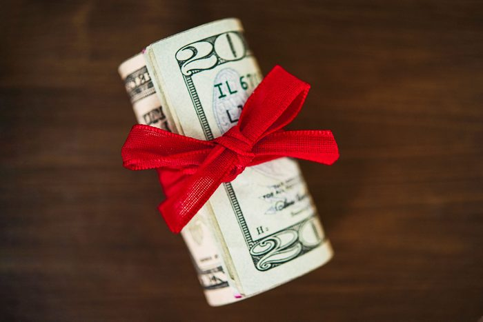 money for a tip rolled up with a red holiday bow on wood background