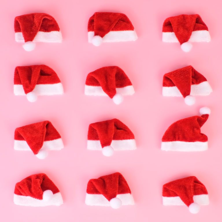 mini santa hats in a grid on pink background
