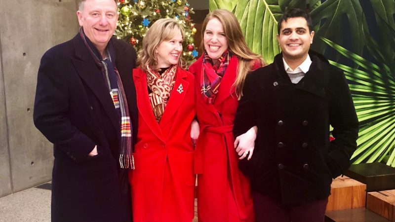 two women in red coats with a man on either side of them stand in front of a christmas background