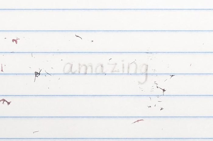 """erased text """"amazing"""" with eraser shavings on loose leaf paper"""