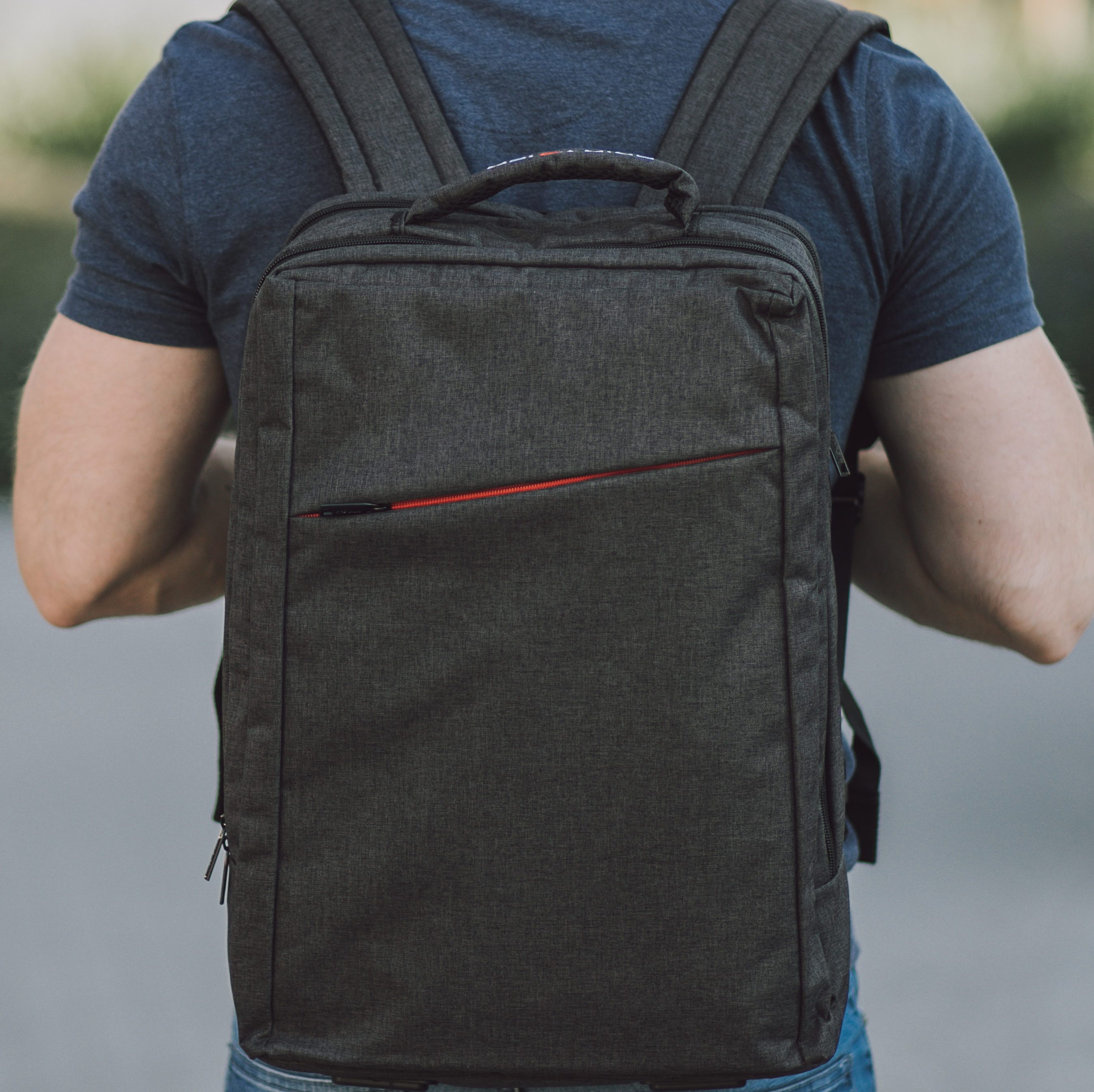 Young man with big and grey laptop case