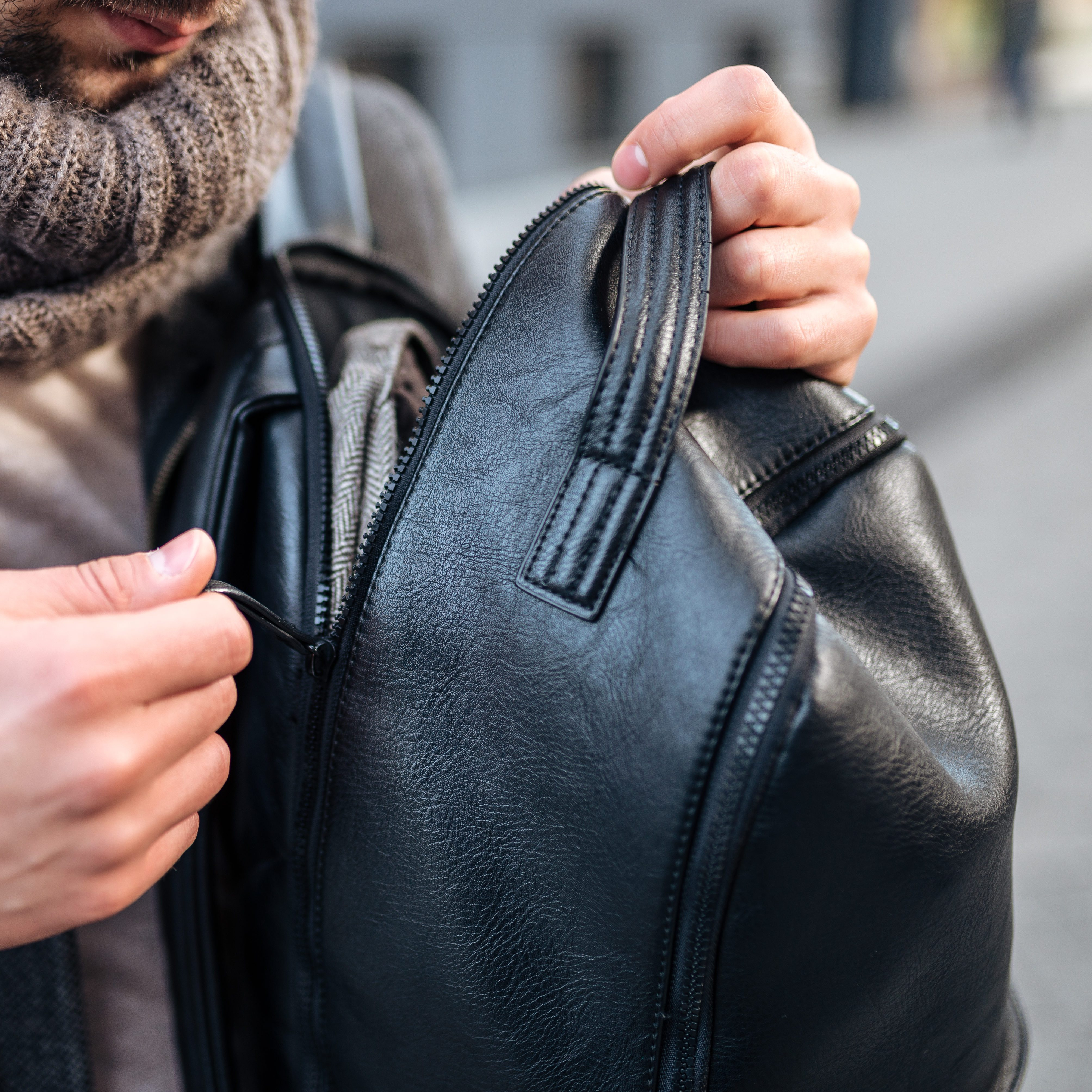 Young man opening his leather backpack.