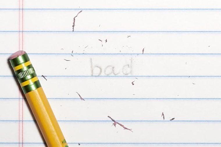 "erased text ""bad"" with eraser shavings on loose leaf paper"