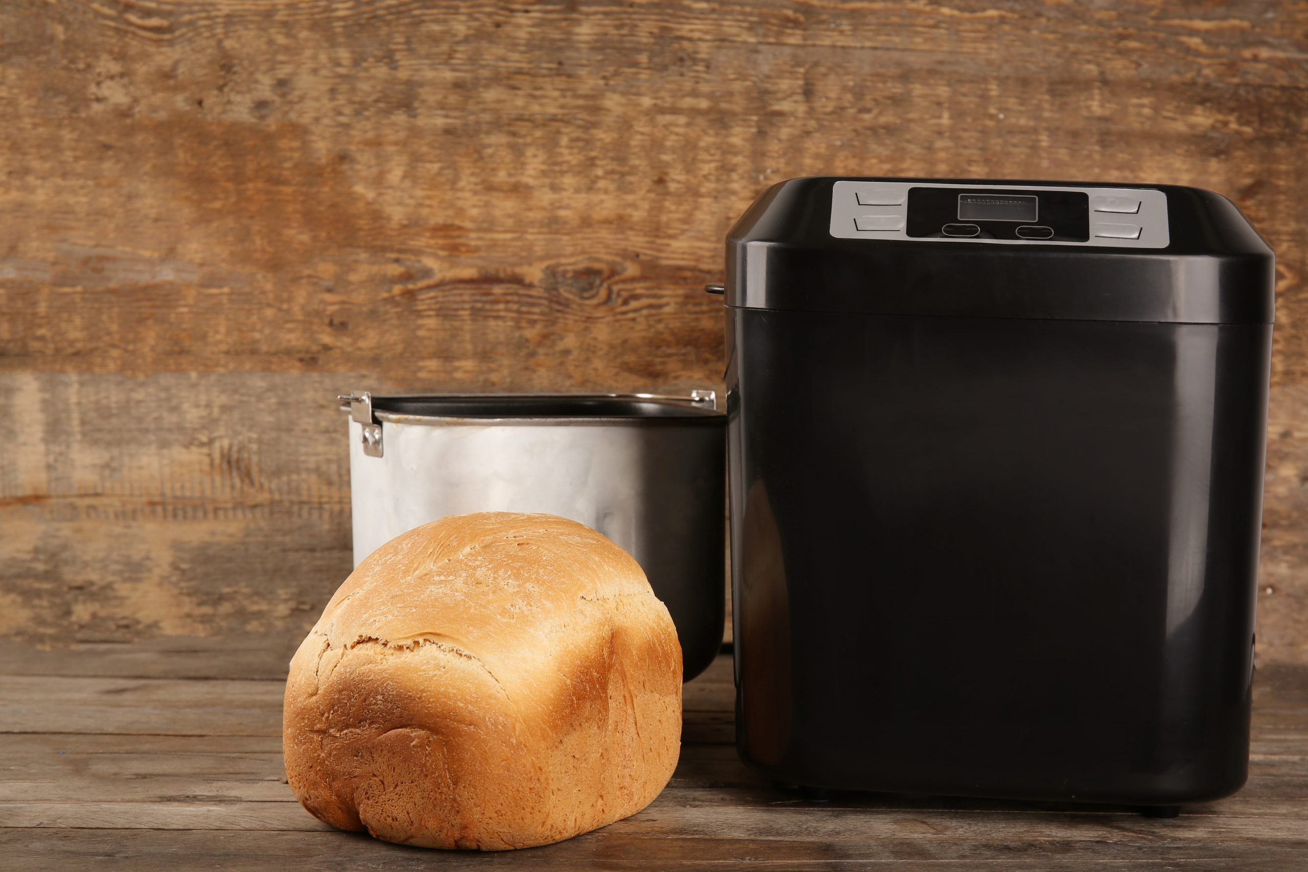 Bread machine with loaf on wooden table