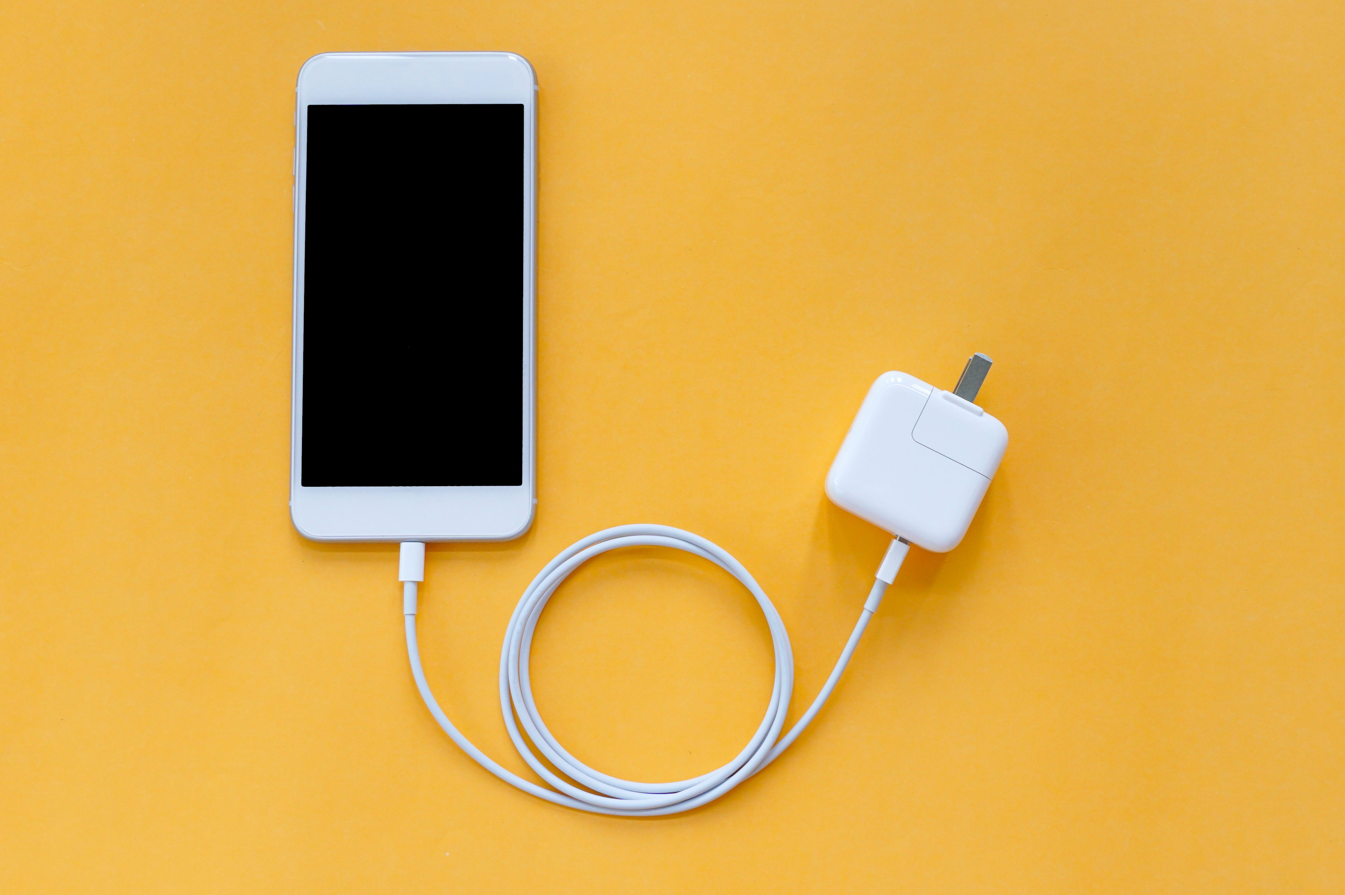 Smartphone Is Connected to Fast Charger Adapter through USB Cable on Orange Background Top View