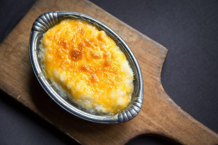 Serving of freshly baked cheese grits in small pewter casserole dish on cutting board.