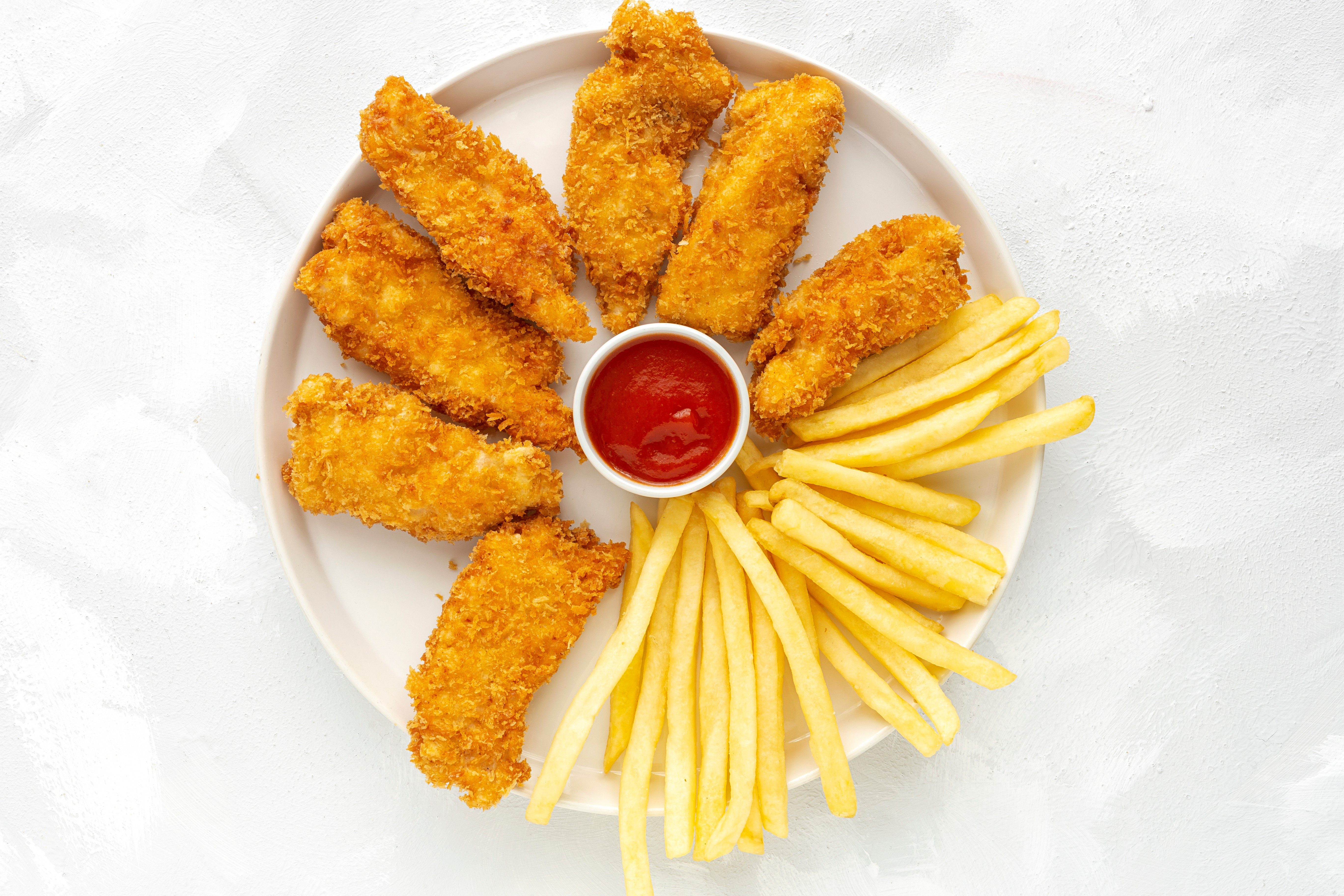 Homemade chicken nuggets battered with panko and French fries views from above on white background. American food
