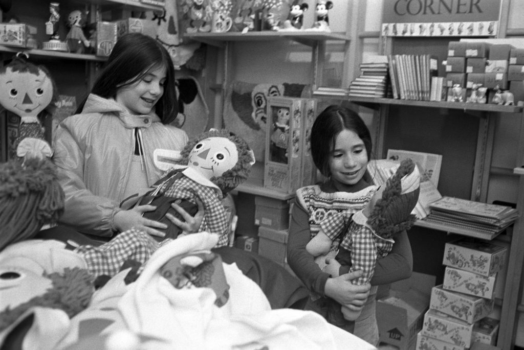 Little girls hold Raggedy Ann dolls in the children's section at Macy's department store christmas