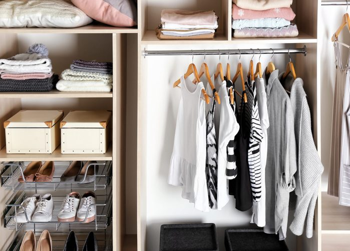 Large wardrobe closet with different clothes, home stuff and shoes