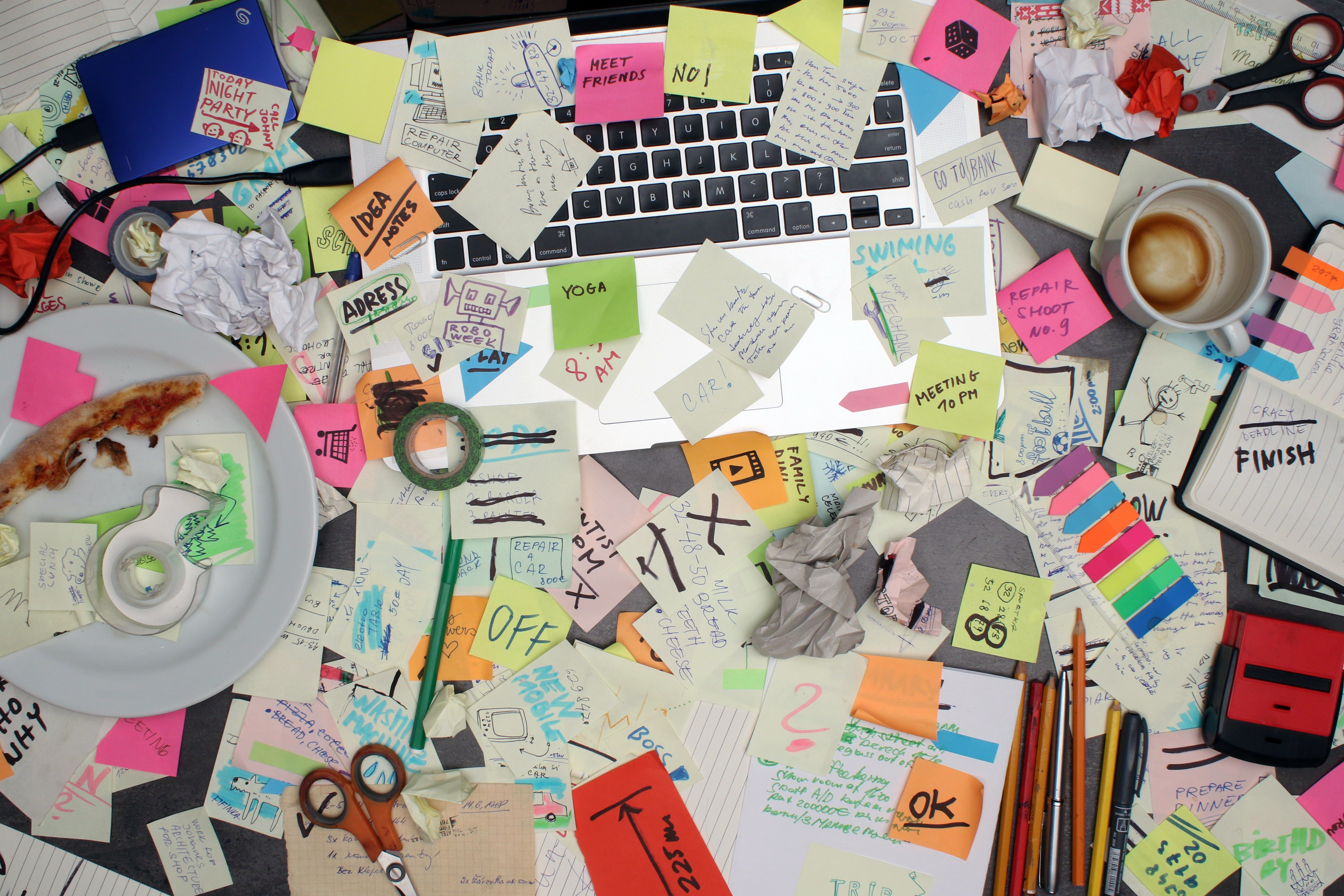 Top view on office desk with laptop computer and notes all around. Overwhelmed with work concept.