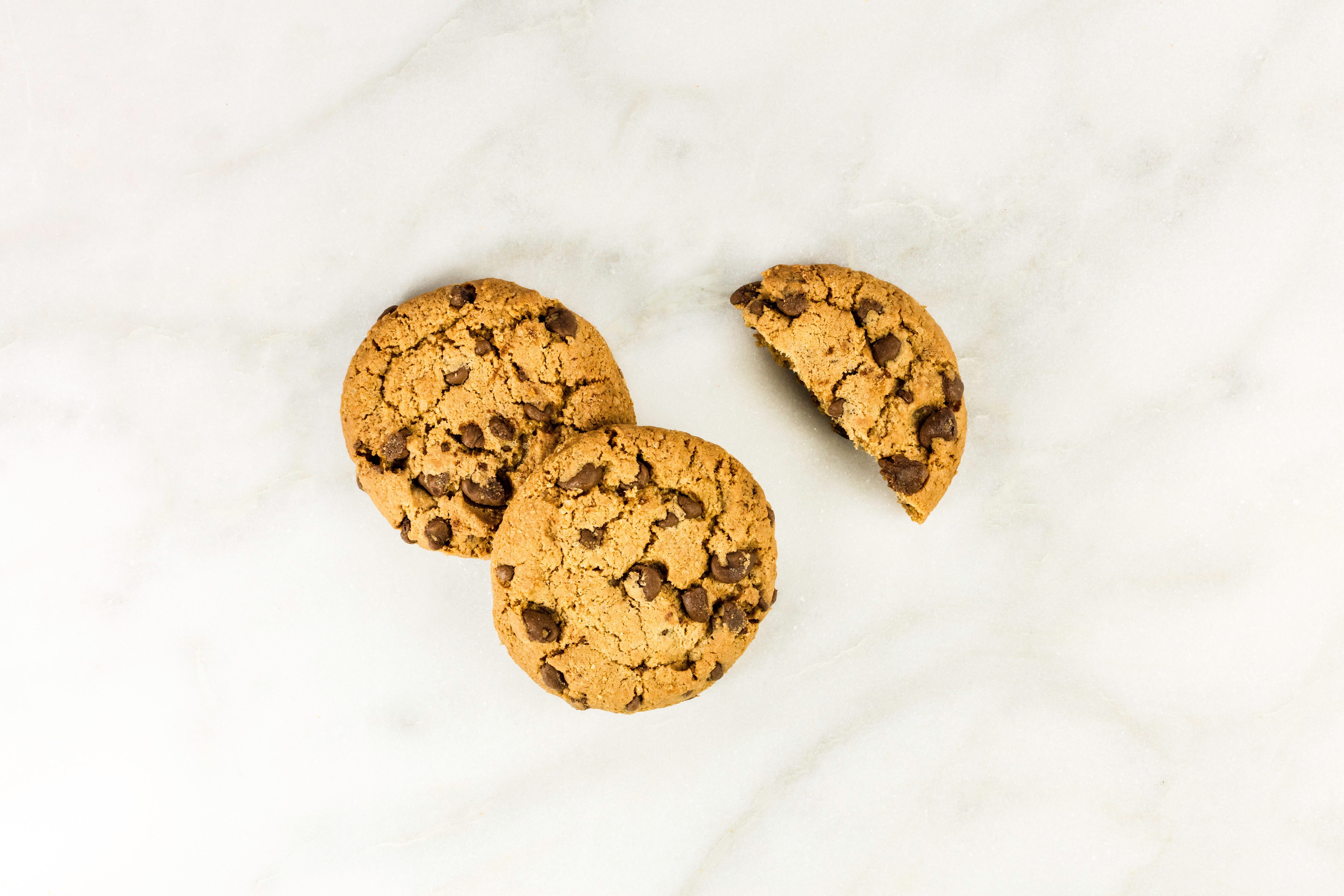 A photo of chocolate chips cookies, shot from above on a white marble background, with a place for text