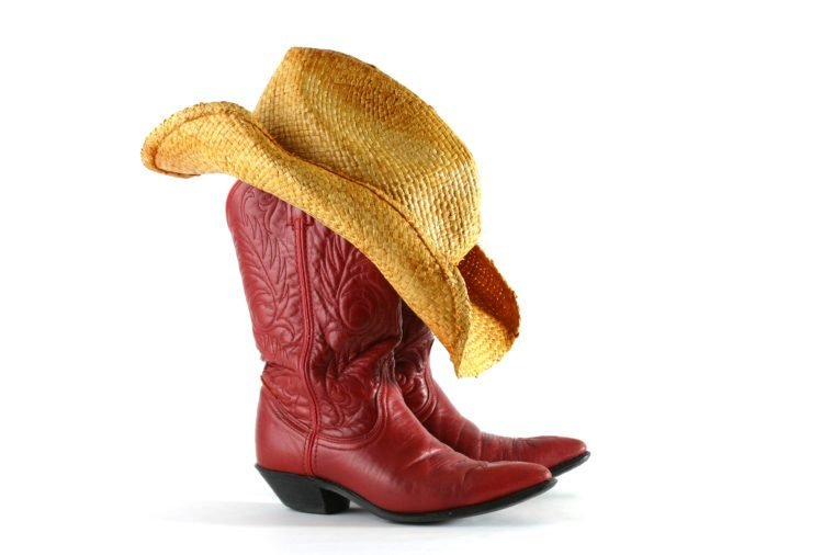 Red leather western boots with straw hat isolated on white