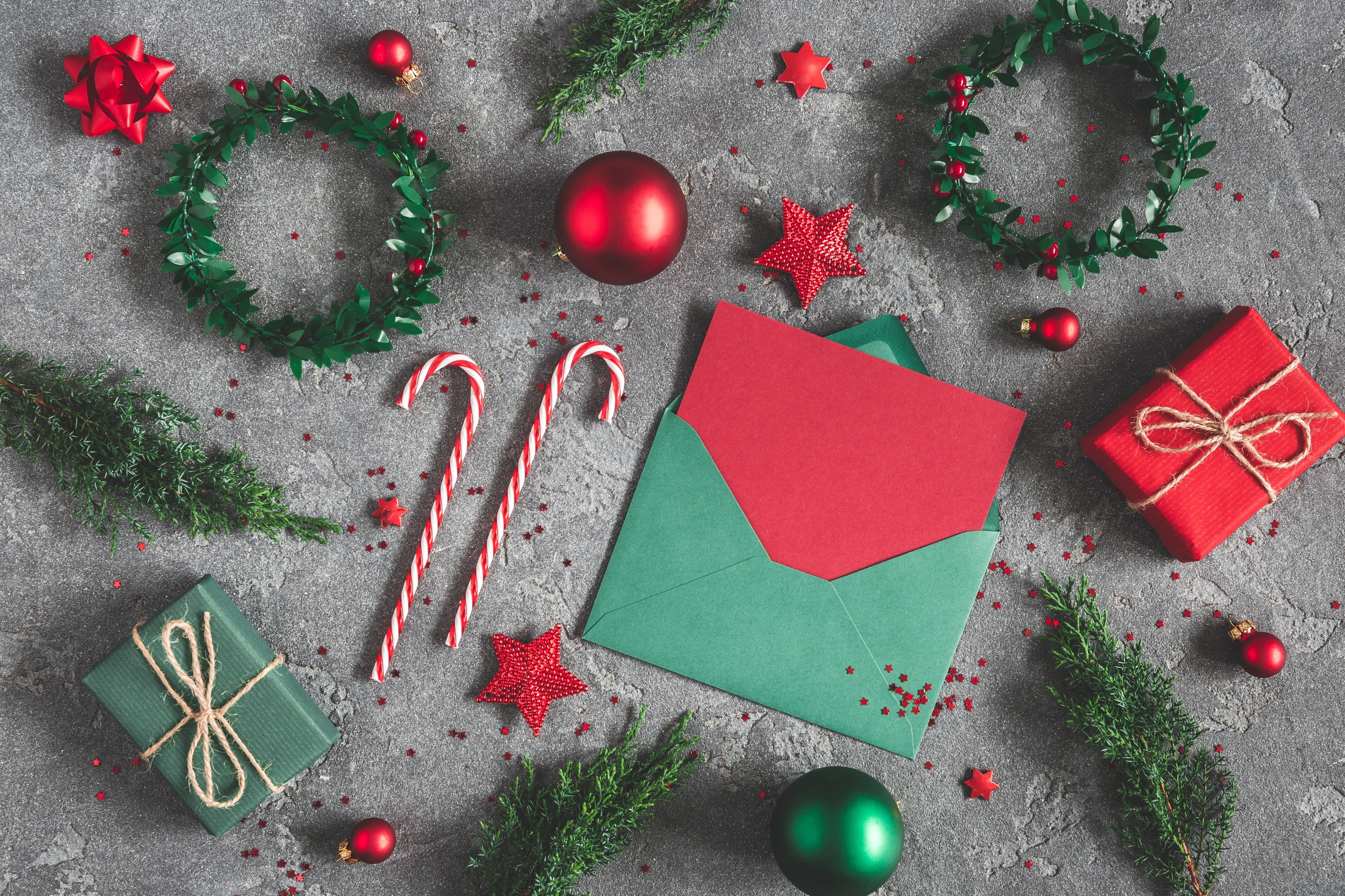 Christmas composition. Gifts, fir tree branches, envelope, card, red decorations on black background. Christmas, winter, new year concept. Flat lay, top view