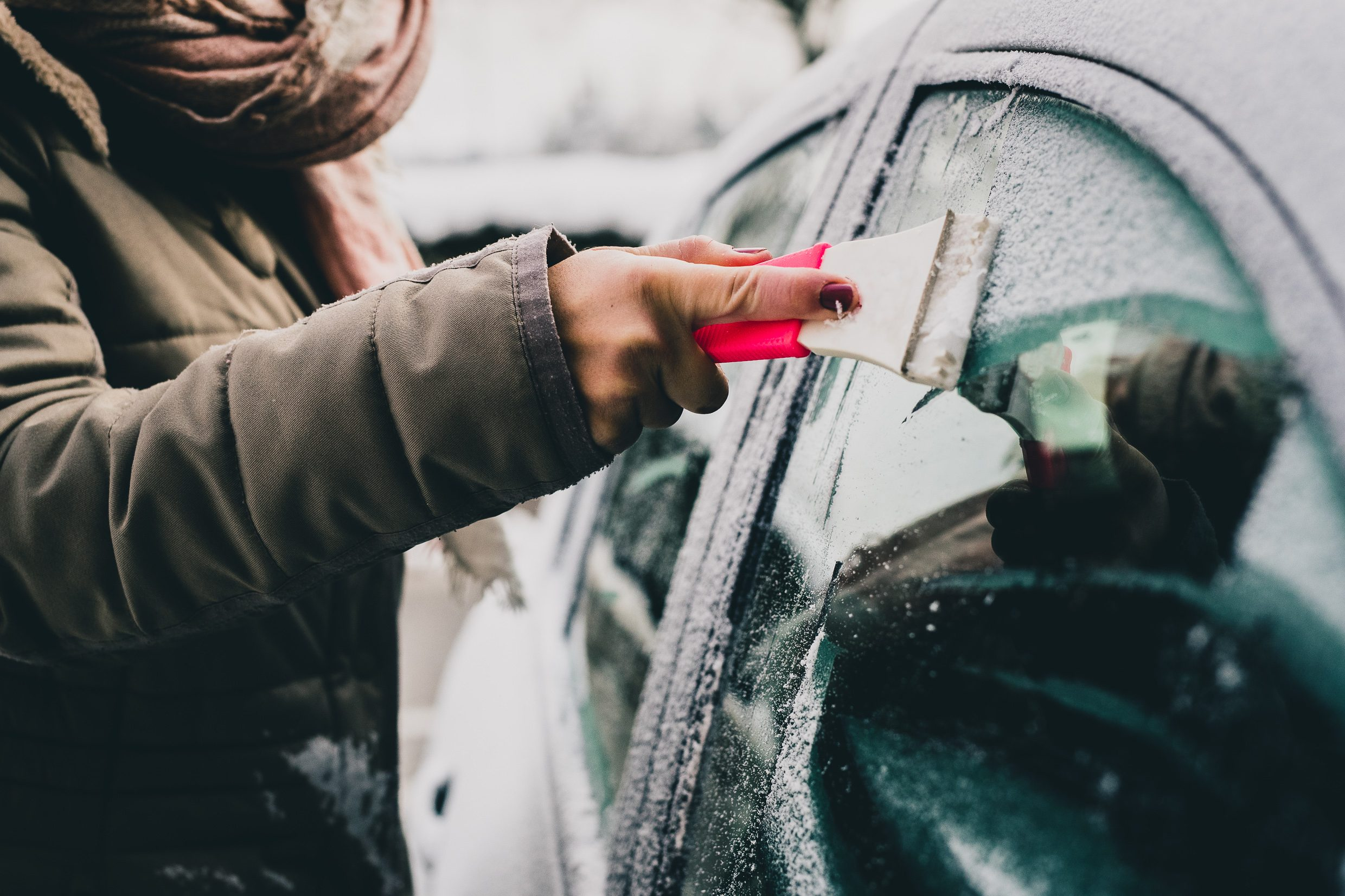 A woman is cleaning an icy window on a car with ice scraper. Focus on the ice scraper. Cold snowy and frosty morning.