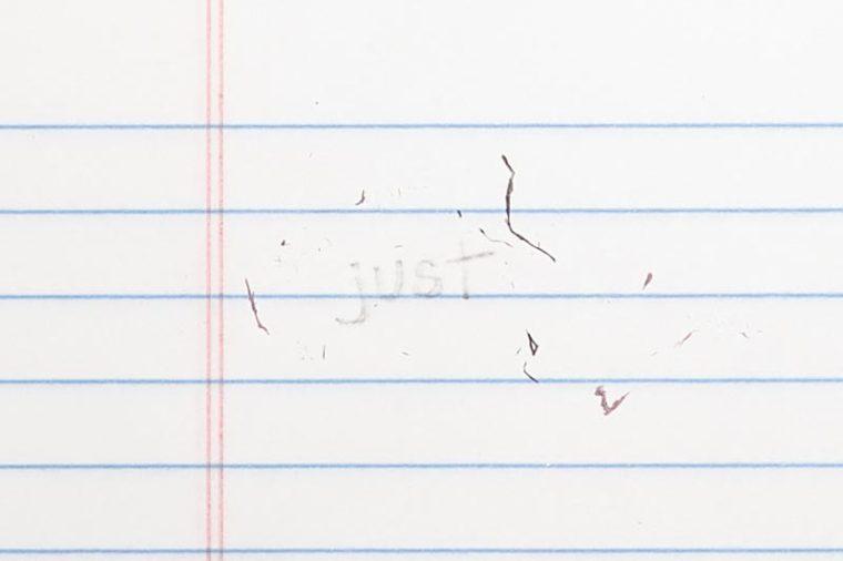 "erased text ""just"" with eraser shavings on loose leaf paper"