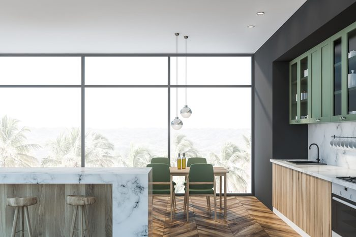 Interior of luxury kitchen with gray and marble walls, wooden floor, large window, wooden countertops, green cupboards, marble bar with stools and dining table with green chairs. 3d rendering