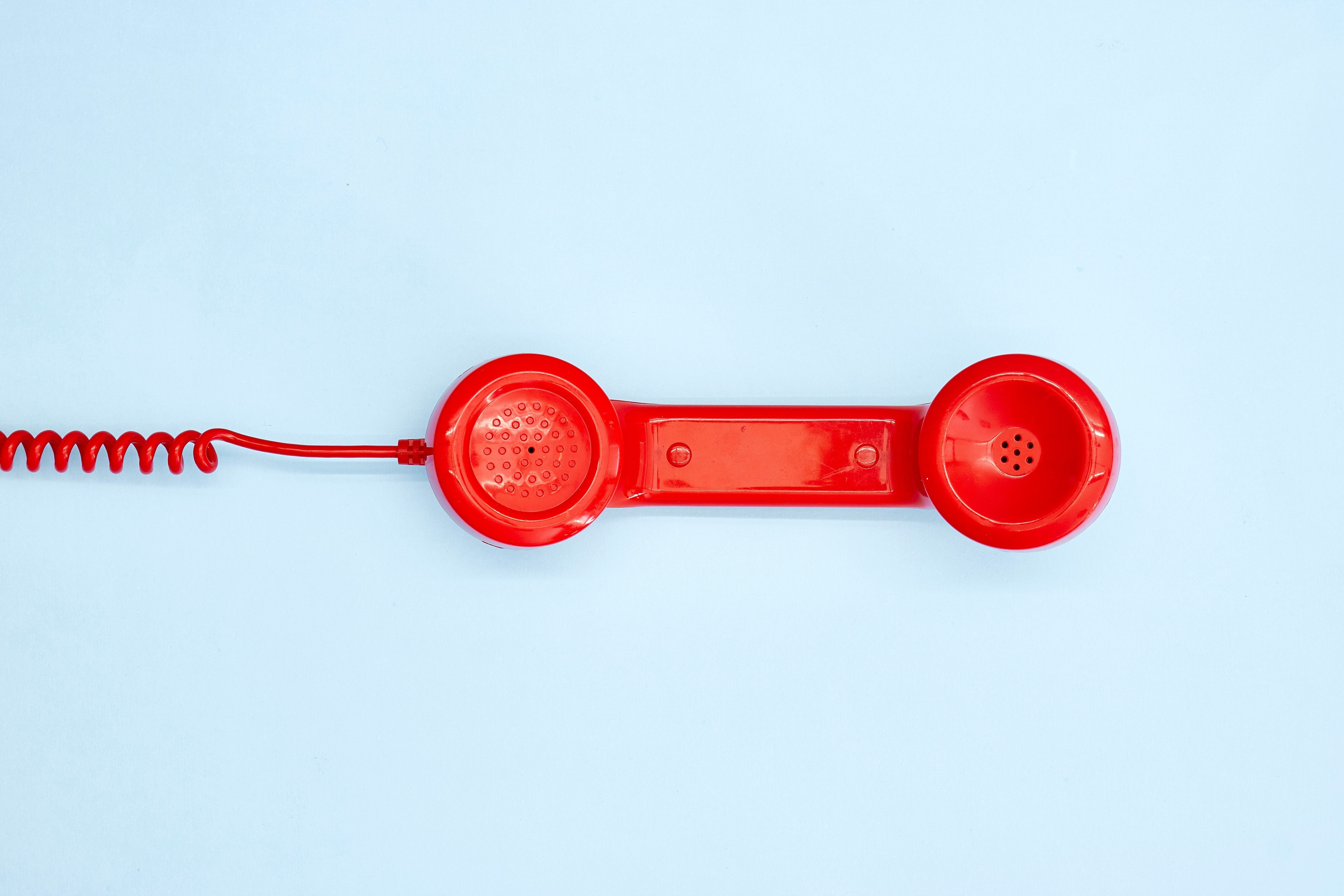 A studio photo of a red rotary telephone
