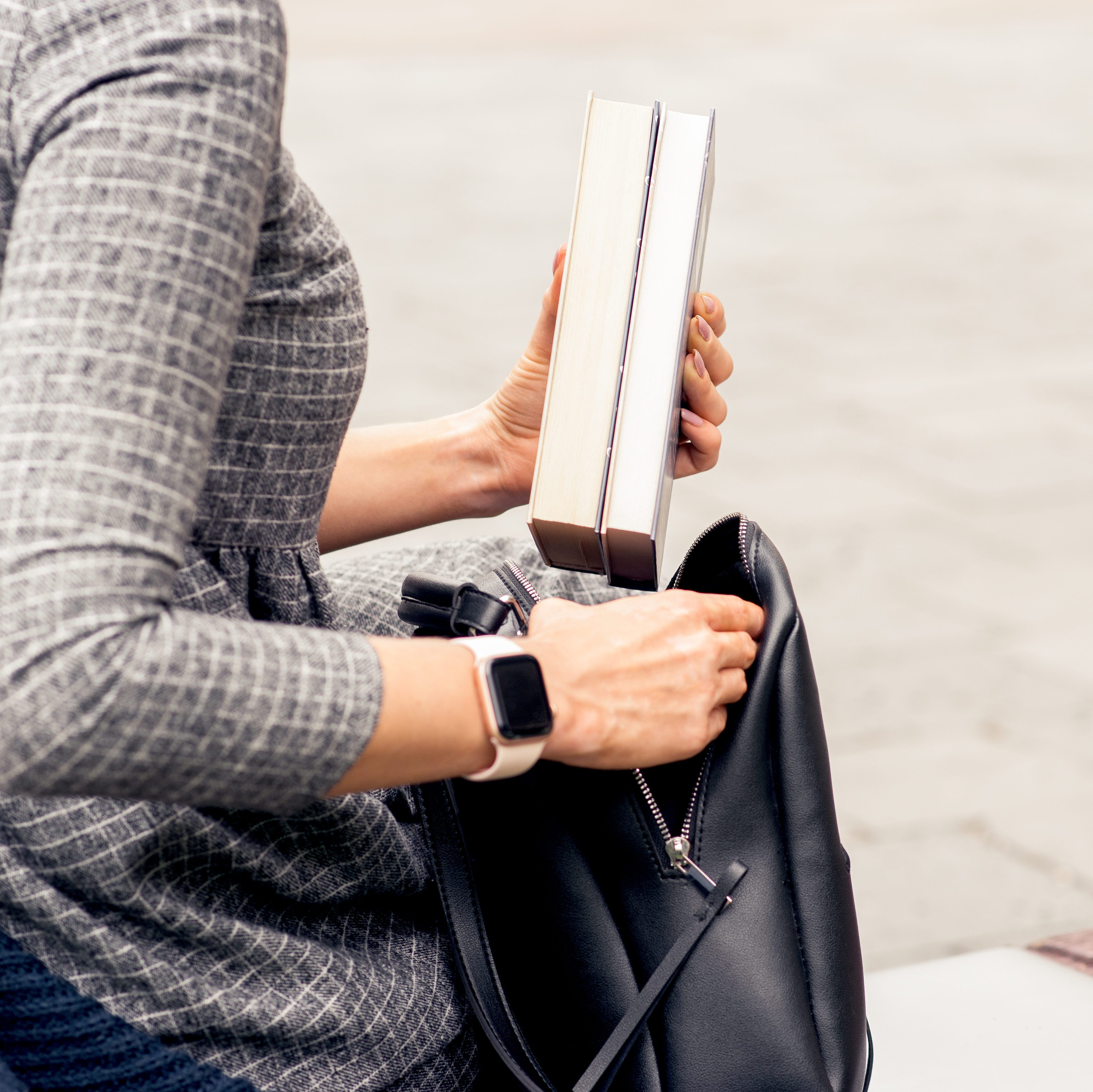 Close up of student's hands puts books into black backpack. Hands of student girl is putting books into backpack outdoors. Student life concept.