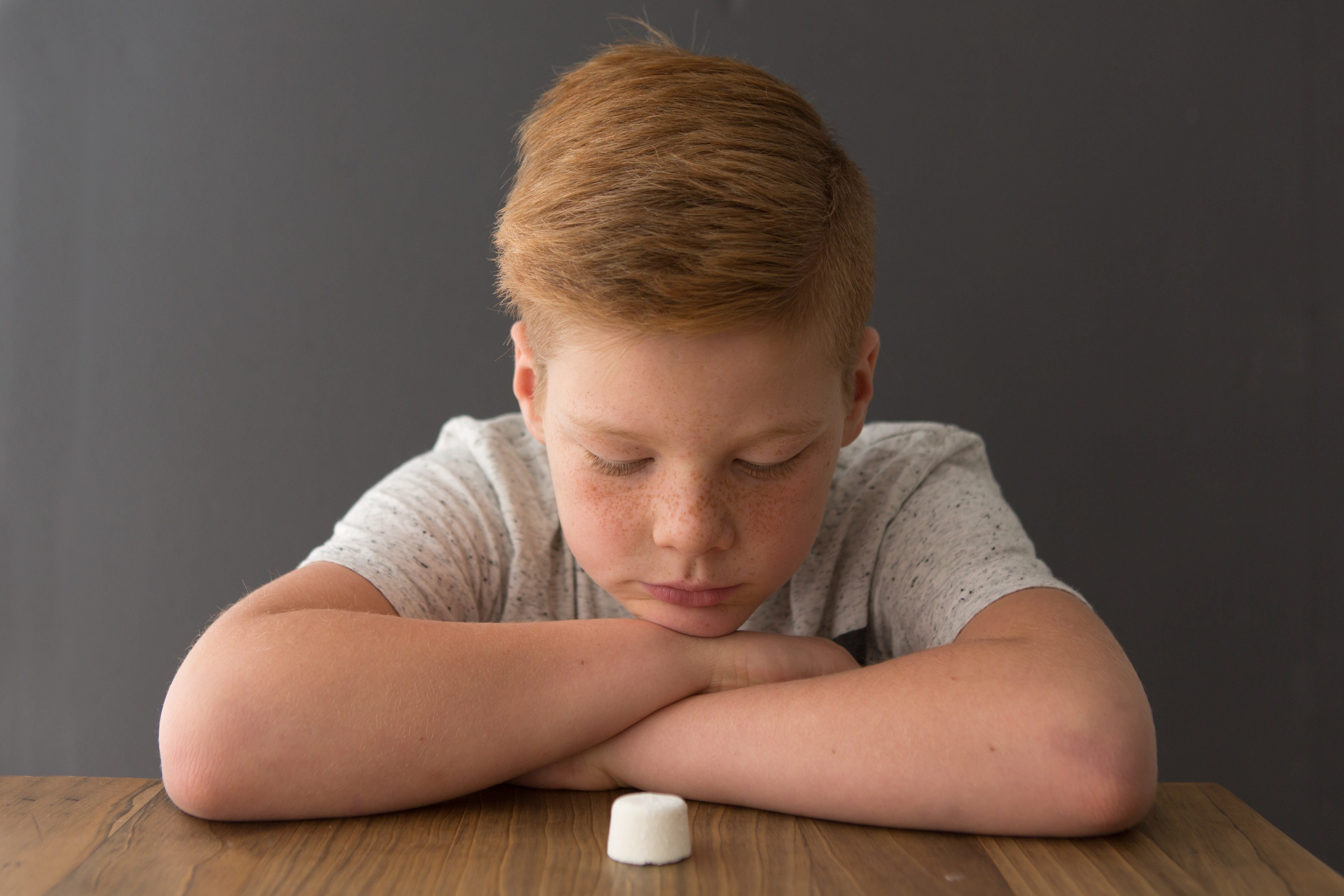 Redhead boy sits at the table opposite a single marshmallow, attempting the marshmallow test