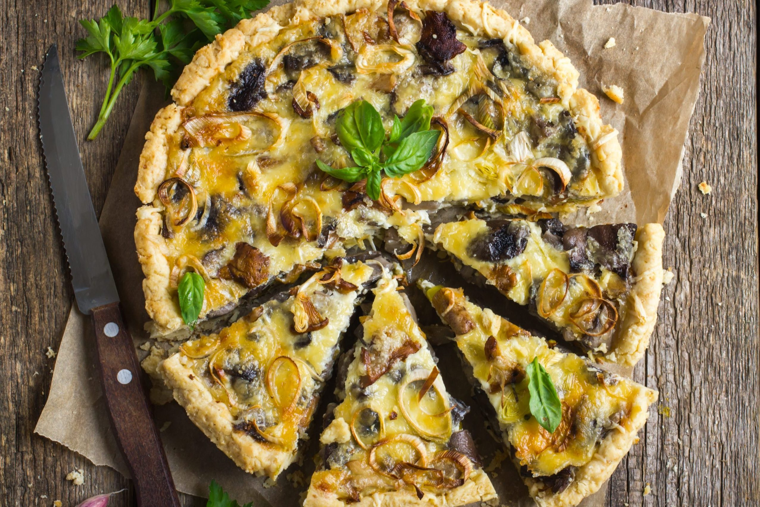 tart with mushrooms, leek and cheese on rustic background