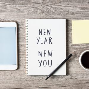 New Year New You text on notepad and smart phone, pen and coffee