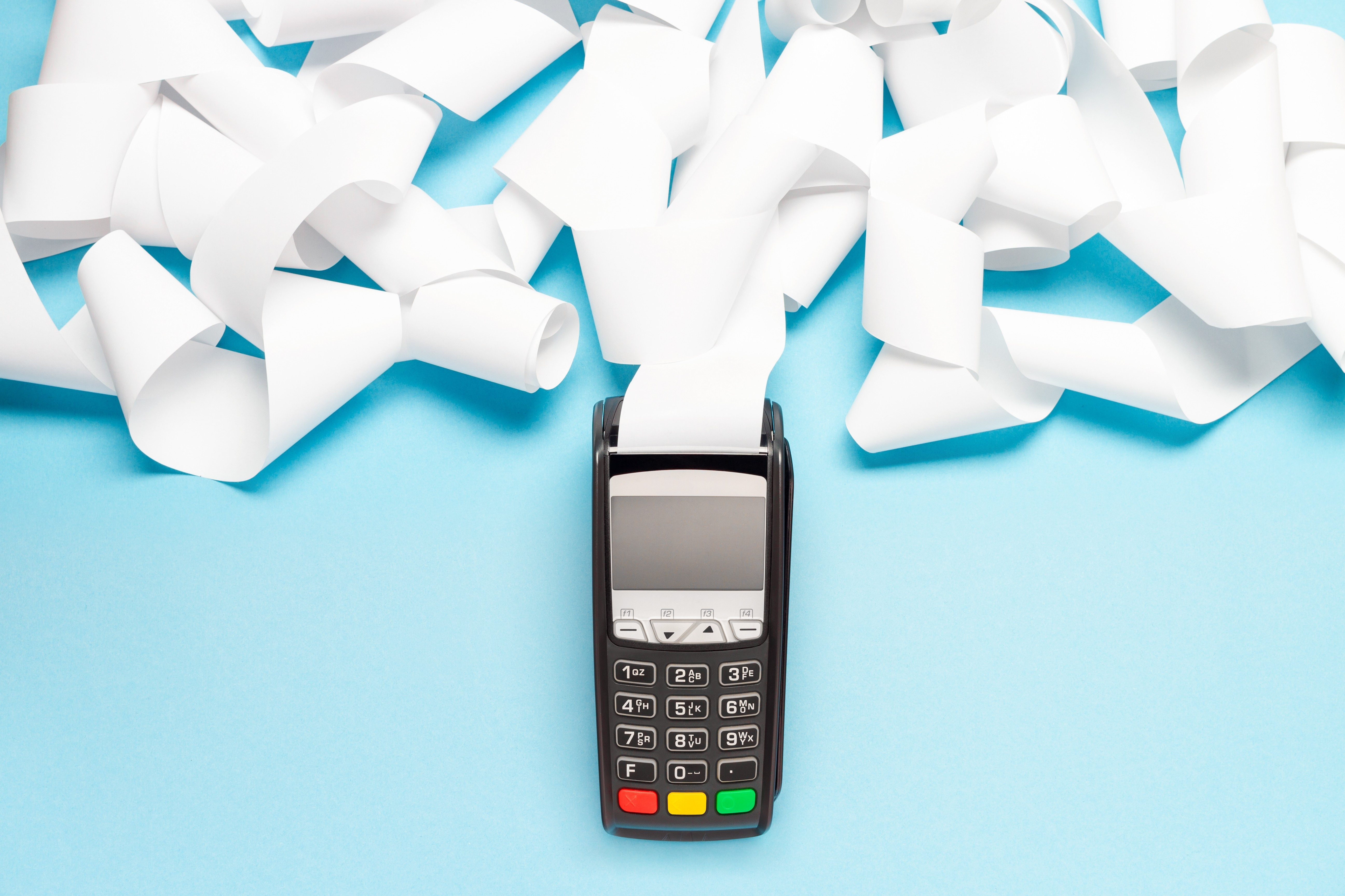 pos terminal with long cash register tape on blue background. shopping theme