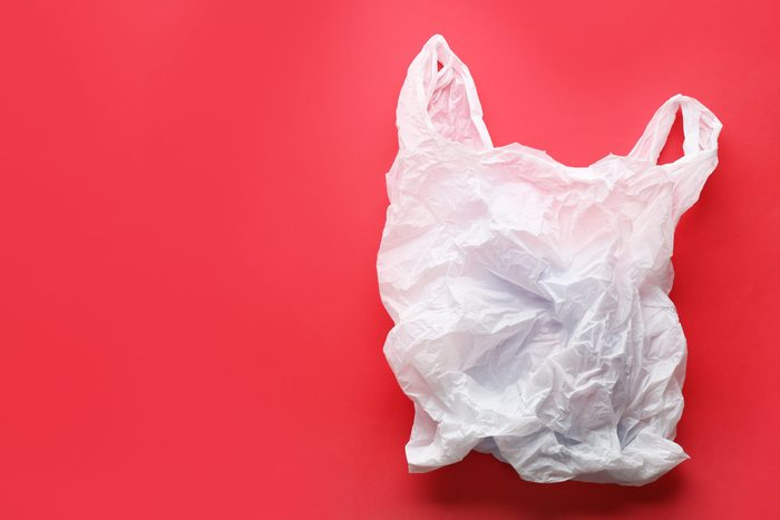 Clear disposable plastic bag on color background. Space for text