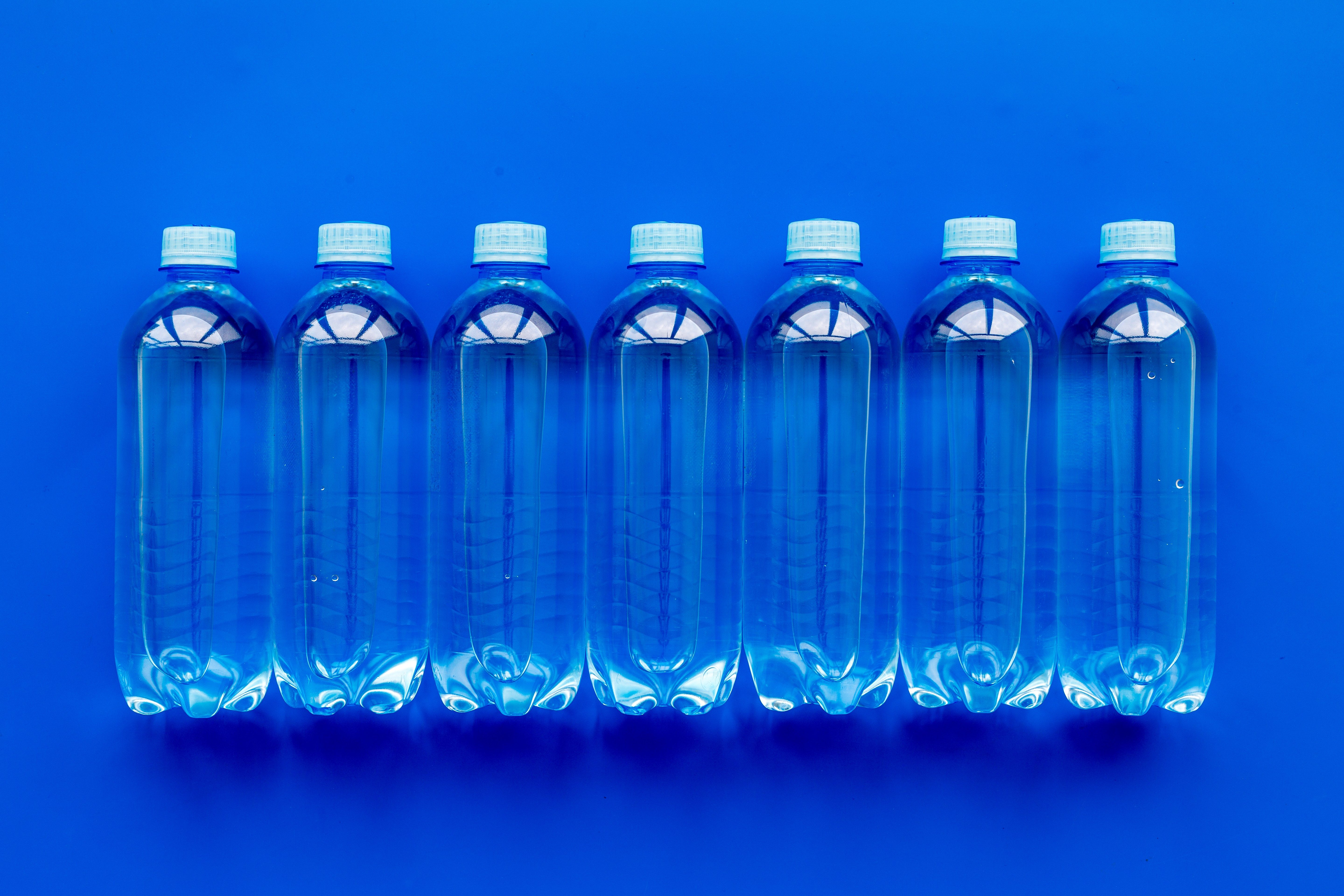 Plastic bottles with pure water on blue background top view