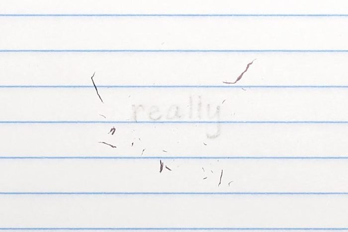 """erased text """"really"""" with eraser shavings on loose leaf paper"""