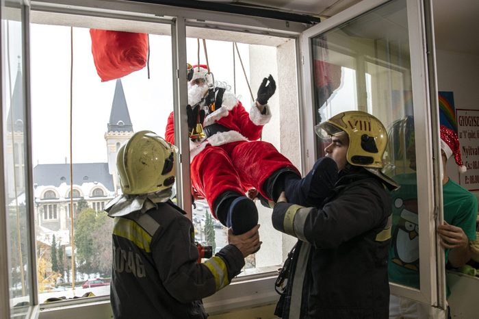 A firefighter dressed as Santa Claus enters through a window into the Pal Heim Children's Hospital in Budapest, Hungary, 06 December 2019. 6 Dec 2019