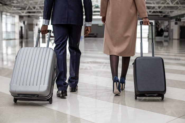 Close-up back view of legs of elegant businesswoman and businessman are going along terminal lounge. They are carrying their luggage to departure area