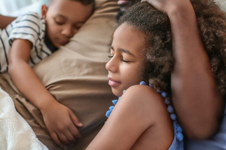 African American man sleeping with his children in bed. Family bedtime