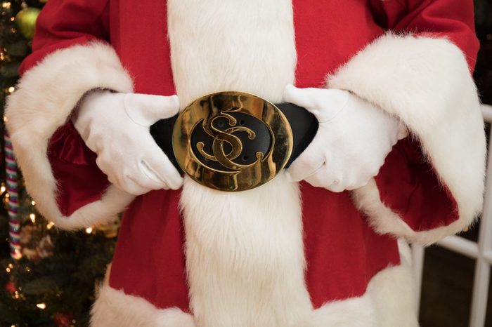 A close up photo of Santa Claus's belly with him holding his belt.