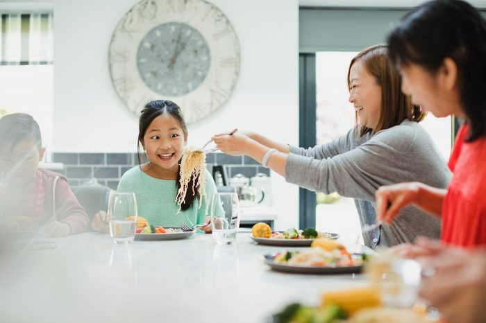 Little girl is looking excited as her mother puts another serving of noodles on her plate at a family dinner at home.