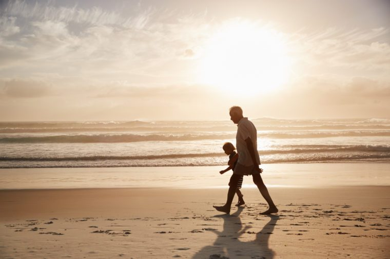 Silhouette Of Grandfather Walking Along Beach With Grandson