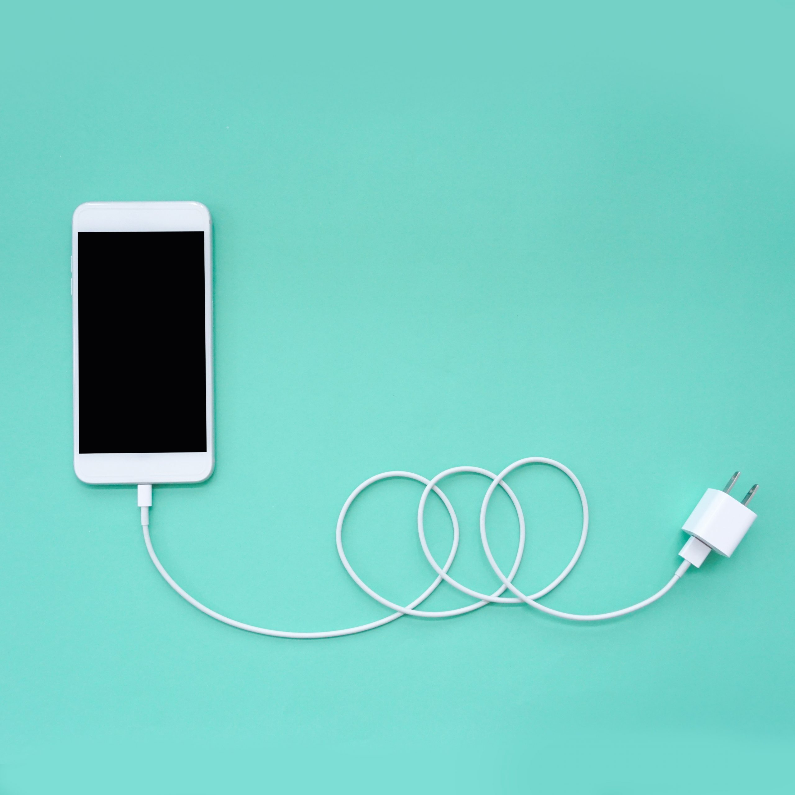 Smartphone Connects to Charger through USB Cable on Turquoise Background Top View; Shutterstock ID 1073489141