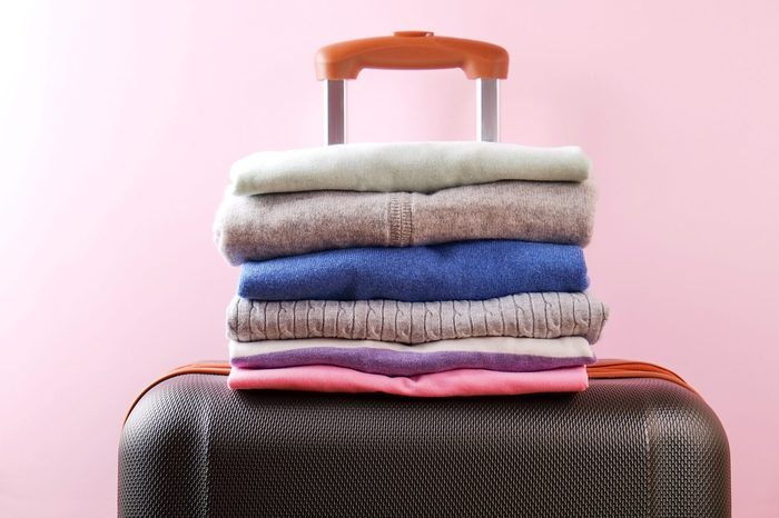 Stack of colorful perfectly folded clothing on plastic suitcase luggage. Pile of different pastel color shirts and sweaters on pale pink wall background. Close up, top view, copy space.