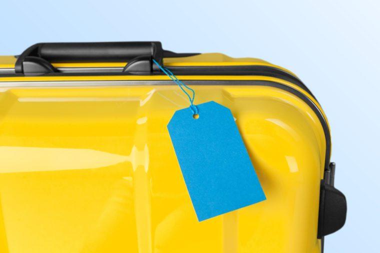 Suitcase on pastel beige background